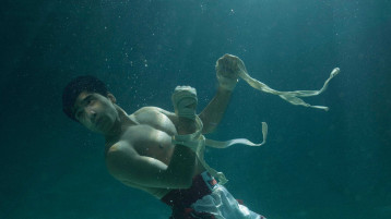 A boxer stands underwater; light streaming through the water