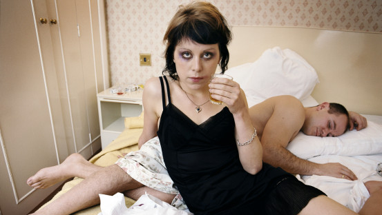 A woman, sprawled on a dishevelled bed looks to camera. She's wearing a black slip, has smeared make-up and is drinking from a whisky tumbler. Behind her on the bed is a man, lying down asleep