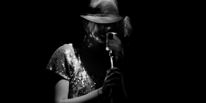 Black and white of Alison Goldfrapp, wearing a sequin top, brimmed hat and singing into a microphone