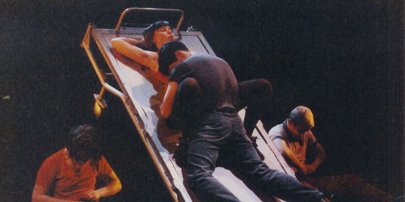 An angled bed. A man is on top of a woman. It looks intimate. Either side of the bed are people sat in chairs with their heads bowed low