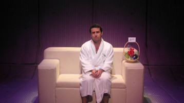 """Man sits on a sofa (in what appears to eb a padded room of some kind) wearing a dressing gown. On the arm of the sofa is a wicker basket of fruit with a note saying """"Welcome"""""""