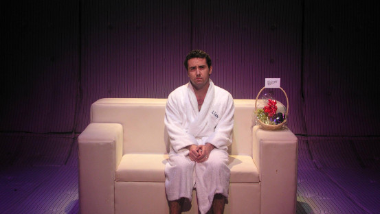"Man sits on a sofa (in what appears to eb a padded room of some kind) wearing a dressing gown. On the arm of the sofa is a wicker basket of fruit with a note saying ""Welcome"""