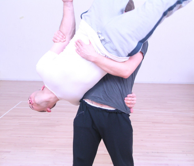 In rehearsal – a man holds another upside down in what appears to be a twisting motion