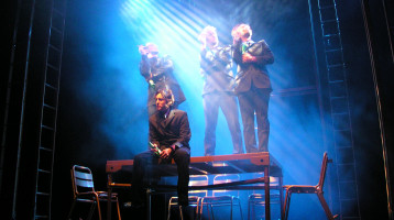 A smoky, blue-lit stage with ladders running up into the darkeness, is set with a rectangular table and five chairs. Three men in suits are stood on the table, holding beers and smoking. A fourth besuited man sits in front of the table, facing the audience. He's also holding a beer, looking pensive