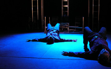 Two men lay on the stage; arms splayed, knees bent. Beyond them, a table lies, upturned.