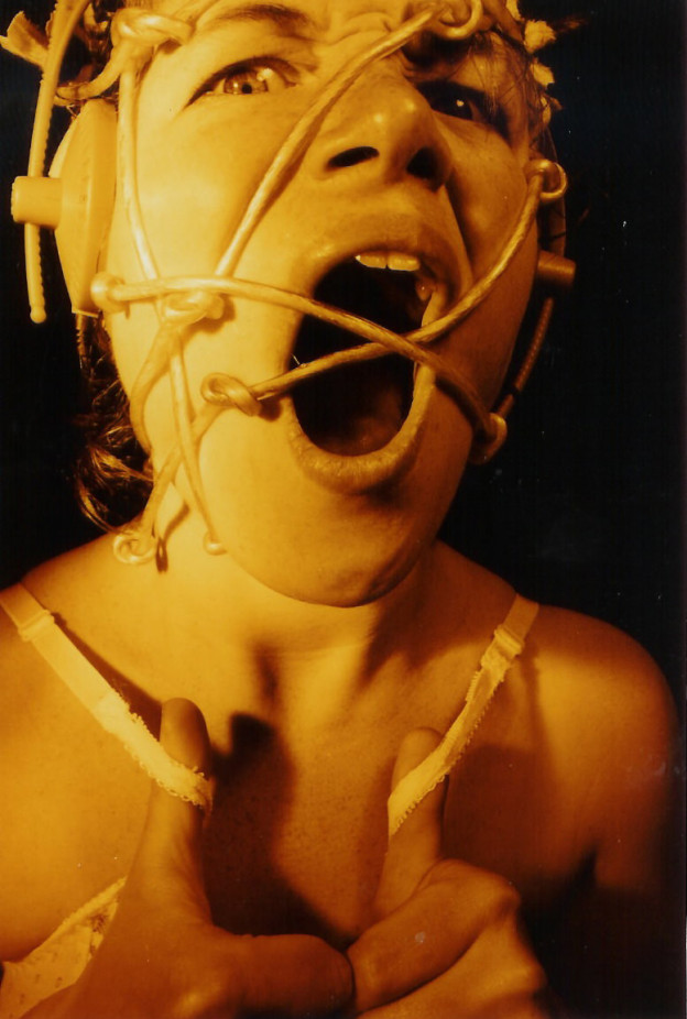 Open-mouthed woman looks to be mid-scream. She's looking to camera; her thumbs pulling her bra straps. Knotted plastic is tangled around her head; and her ears are covered by headphones