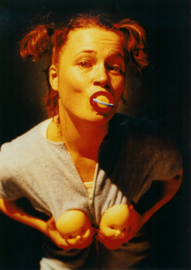 Woman in pig-tails is sucking a dummy, looking to camera. Shes's holding the plastic faces of two baby dolls to her breasts.