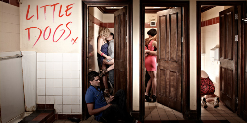 Three open cubicle doors in a public lavatory. Inside two of the cubicles there are couples kissing. In the final cubicle a woman is sat, kneeing on the floor bent over the toilet