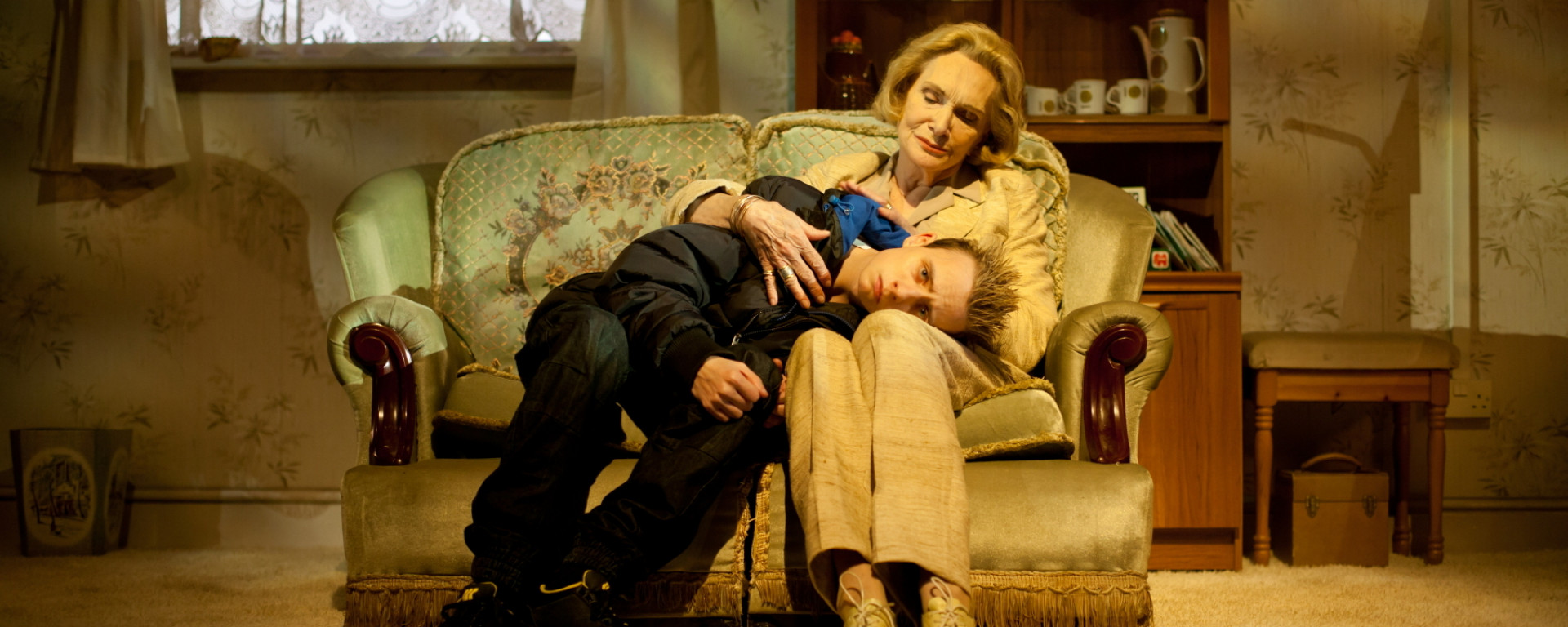 An older woman and younger man sit on a sofa in a living room. The woman is cradling the young man's head on her lap. He looks upset; she's comforting him