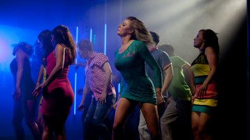 People dance in formation in a nightclub setting