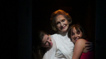 Two young clubbers hug an older lady who's dressed in a white gown