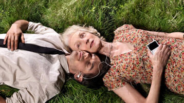 Overhead shot of two people laying on grass. With heads together, they are sharing earbuds. The woman has her eyes open, while the man has his closed. Both are smiling.