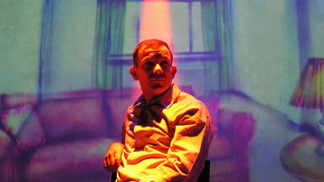 A man sits on a chair – his arm resting on its back – looking into the middle distance. He's under a coloured spotlight and behind him is a projected illustration of a living room with sofa, window, and table with lamp