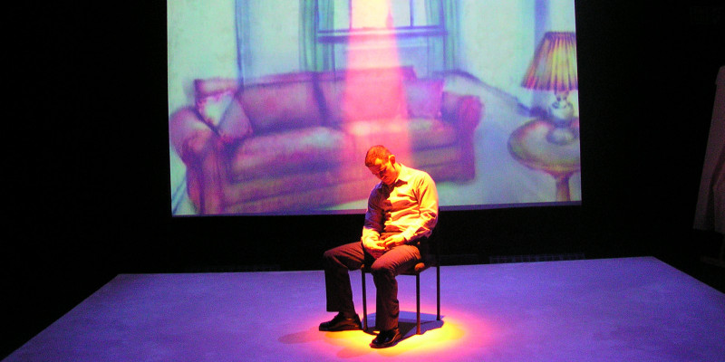 A man sits, head down, on a chair on an empty stage. He's under a pink spotlight, and behind him is a projected illustration of a sofa, table with lamp and window.