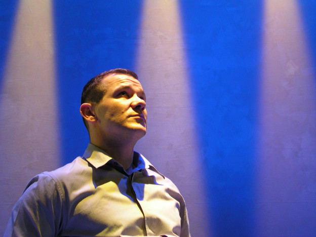 A man stands tall, looking up into the middle distance. He's in front of a blue backdrop with three spotlights streaming down it.
