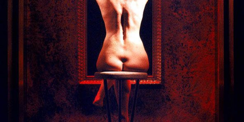 A naked woman sits with her back to the camera, on a high stool. Her legs are crossed and her hands are hugged around her shoulders. She's facing towards a large, ornate picture frame – it's not celar what this frame holds.