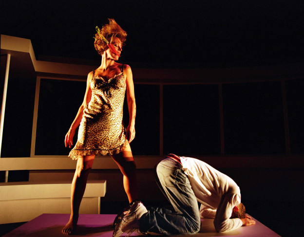 Woman in an animal-print slip with a carrot in her mouth stands over a man. He's on his knees, head and arms to the ground, facing away from her