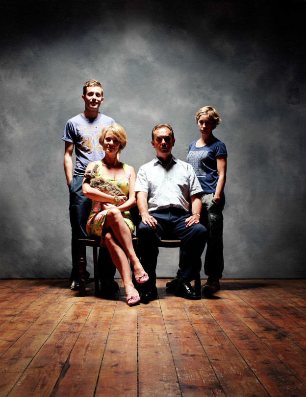 A portrait of four people. An older man and woman sit on chairs, with a younger man and woman stood behind them. The older woman and younger man are smiling; the older man and younger woman are not. Everyone's faces are somewhat in shadow which suggests menace and mild peril
