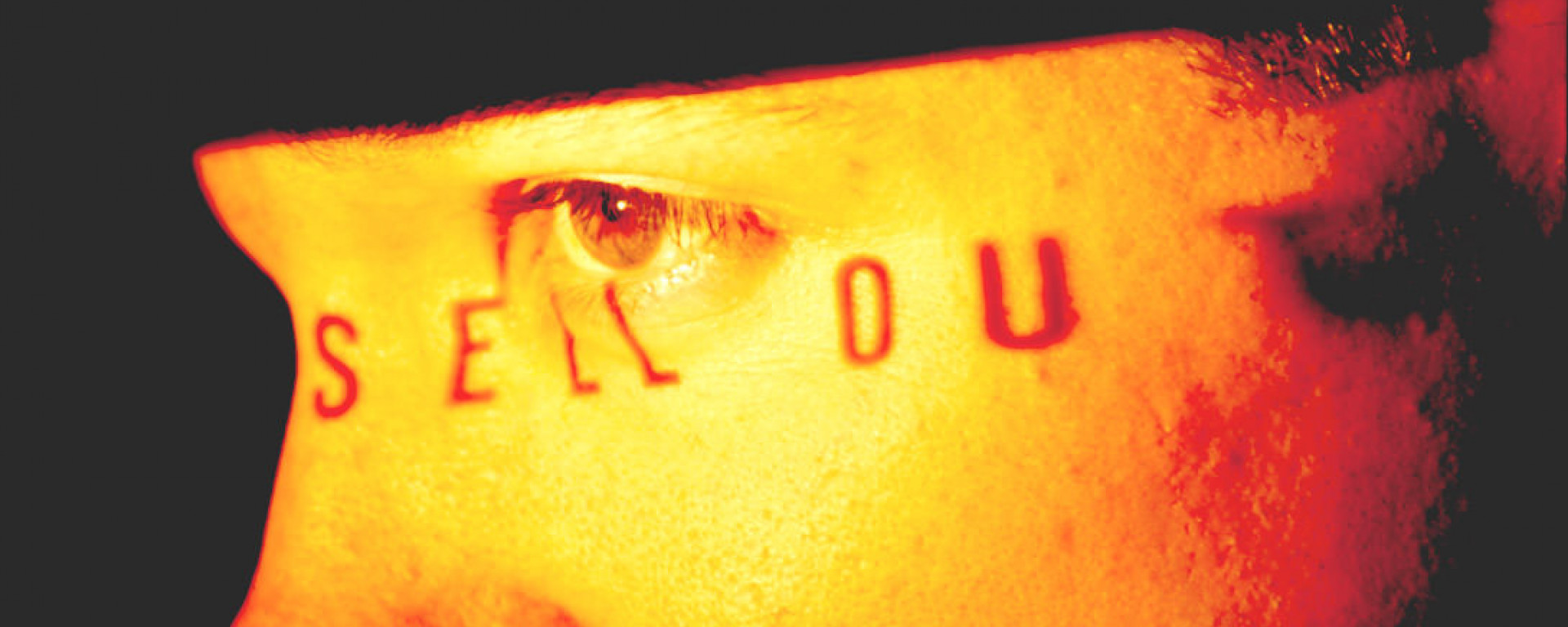 Extreme close-up of a man's profile – just his eye and part of his nose are visible. The words 'Sell Out' are projected across his skin