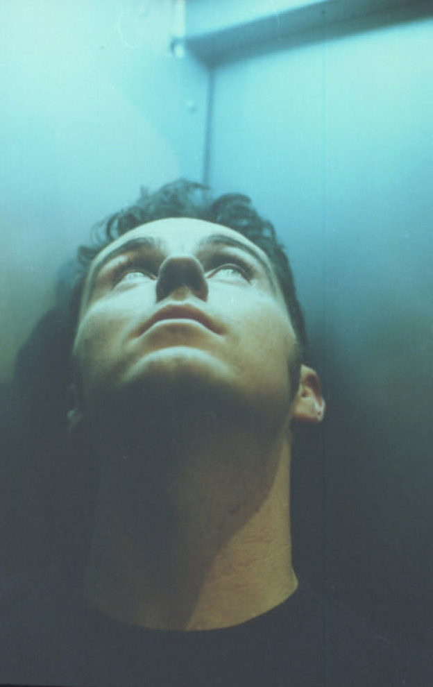 Headshot of man standing in a corner (of a lift?) looking upwards, towards a light