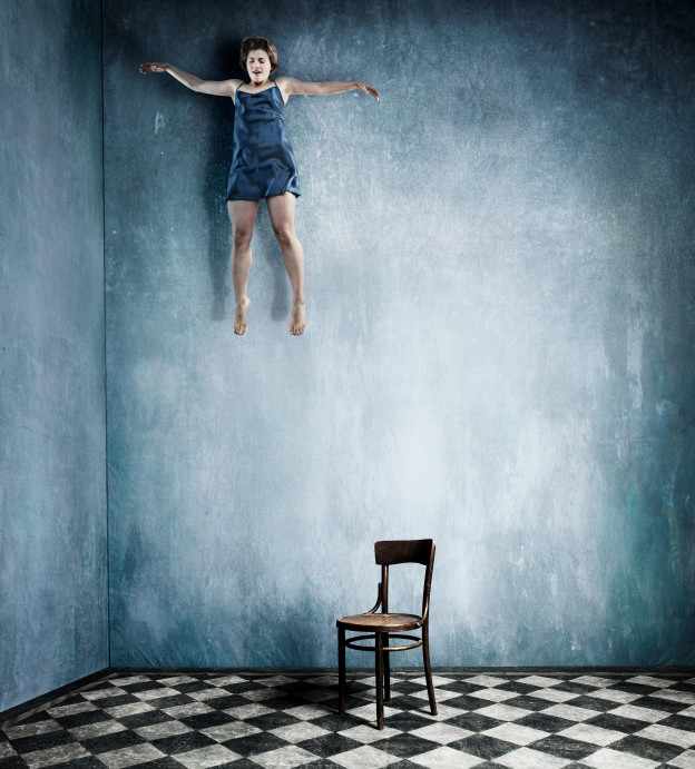 Wide shot of a high-ceilinged room with chequered floor. On the floor, a wooden chair. Invisibly suspended above the chair and to the left is a woman; her eyes closed, mouth slightly open, and arms outstretched. She looks as though she's floating