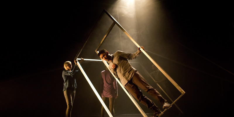 A man stands within a cuboid frame, tilted on its edge and held by two other performers