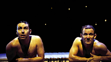 Two men appear as if they've just emerged from a swimming pool; supporting themselves on the side, and looking towards an unseen audience