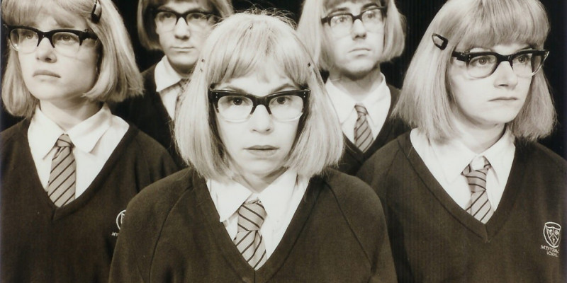 Five people wearing school uniforms, thick-rimmed spectacles, and blonde bobbed wigs. The three in the front are women; two behind them are men