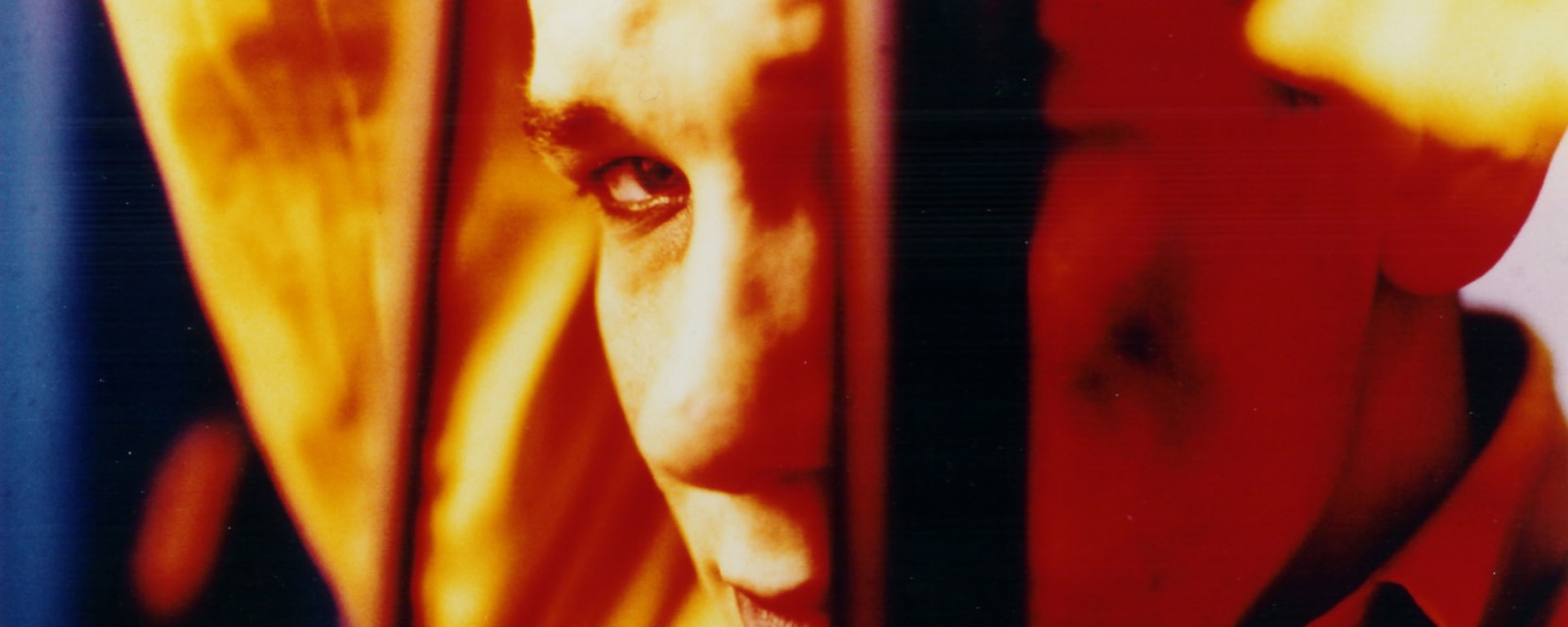 Close-up of a man's face in saturated, acidic orange tones. His looking to camera, his face obscured by what appears to be a vertical bar of some kind. His expression is that of someone lost