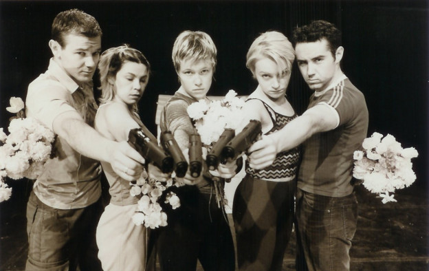 Five people each hold a pistol; bringing them together to point towards the camera. In their olterh hands they hold bunches of flowers